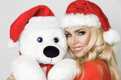 在圣诞老人帽子穿戴的美好的性感的白肤金发的女性模型拥抱在一个红色盖帽Christm的一个白色玩具熊 免版税库存照片