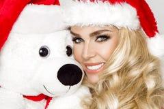 在圣诞老人帽子穿戴的美好的性感的白肤金发的女性模型拥抱在一个红色盖帽Christm的一个白色玩具熊 免版税库存图片