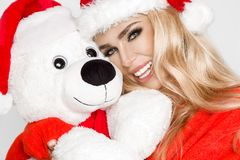 在圣诞老人帽子穿戴的美好的性感的白肤金发的女性模型拥抱在一个红色盖帽Christm的一个白色玩具熊 库存照片