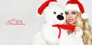 在圣诞老人帽子穿戴的美好的性感的白肤金发的女性模型拥抱在一个红色盖帽Christm的一个白色玩具熊 免版税图库摄影