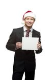 在圣诞老人帽子藏品符号的微笑的生意人 免版税库存图片