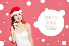 在圣诞老人帽子认为在桃红色背景的愉快的激动的少妇 空白礼服的逗人喜爱的女孩 长的头发和红色嘴唇 Happ 免版税库存图片