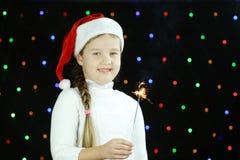 在圣诞老人帽子,女孩拿着闪烁发光物火 库存照片