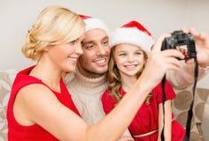 在圣诞老人拍照片的帮手帽子的微笑的家庭 免版税库存图片