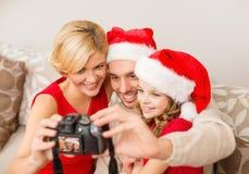 在圣诞老人拍照片的帮手帽子的微笑的家庭 库存图片