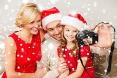 在圣诞老人拍照片的帮手帽子的微笑的家庭 图库摄影