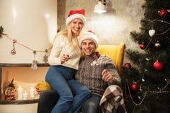 在圣诞老人拿着闪烁发光物的` s帽子的迷人的年轻夫妇,看 库存照片