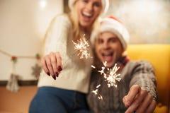 在圣诞老人拿着闪烁发光物,有选择性的f的` s帽子的愉快的年轻夫妇 免版税库存图片