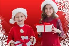 在圣诞老人的两个愉快的孩子打扮拿着圣诞节礼物 免版税库存照片