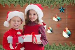 在圣诞老人的两个愉快的孩子打扮拿着圣诞节礼物 库存图片