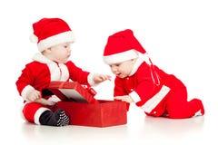 在圣诞老人的二个滑稽的孩子穿衣与礼物盒 免版税图库摄影