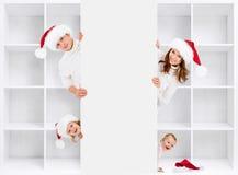 在圣诞老人的帽子的圣诞节家庭有棚架的 免版税库存照片