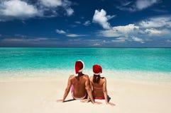 在圣诞老人的帽子的夫妇在马尔代夫的一个海滩 免版税库存图片