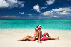 在圣诞老人的帽子的夫妇在马尔代夫的一个海滩 免版税图库摄影