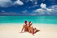 在圣诞老人的帽子的夫妇在马尔代夫的一个海滩 图库摄影