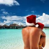 在圣诞老人的帽子的夫妇在马尔代夫的一个海滩 免版税库存照片