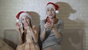 在圣诞老人的帽子的愉快的孩子是笑和使用与第2019年在他们的手上 他们坐沙发反对a 股票录像