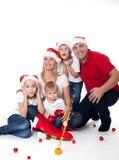 在圣诞老人的帽子的愉快的逗人喜爱的家庭 免版税图库摄影