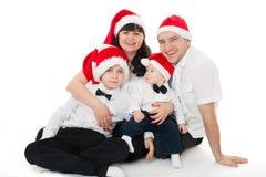 在圣诞老人的帽子的愉快的逗人喜爱的家庭 免版税库存图片