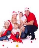 在圣诞老人的帽子的愉快的逗人喜爱的家庭 图库摄影