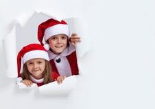 在圣诞老人的愉快的孩子通过在纸的孔装备看 图库摄影