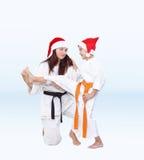 在圣诞老人盖帽母亲训练儿子反撞力腿 库存图片