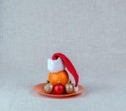 在圣诞老人盖帽的桔子  免版税库存照片