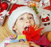在圣诞老人红色帽子的小逗人喜爱的孩子有手工制造的 免版税库存照片
