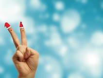 在圣诞老人红色空白帽子穿戴的手指。 库存图片