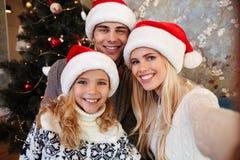 在圣诞老人采取selfie的` s帽子的可爱的年轻家庭在圣诞节附近 免版税库存图片
