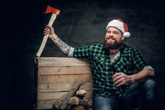 在圣诞老人` s帽子,饮用的啤酒的肥腻有胡子的男性 库存照片
