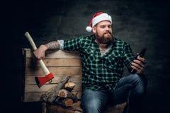 在圣诞老人` s帽子,饮用的啤酒的肥腻有胡子的男性 免版税库存照片