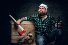 在圣诞老人` s帽子,饮用的啤酒的肥腻有胡子的男性 免版税图库摄影