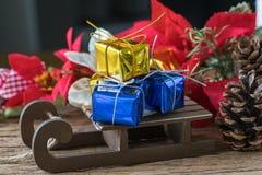 在圣诞老人slei的微型金黄和蓝色当前礼物盒 库存图片