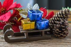 在圣诞老人slei的微型金黄和蓝色当前礼物盒 免版税库存图片