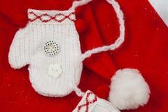 在圣诞老人xmas帽子的一个微型手套 免版税图库摄影