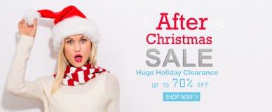在圣诞节与妇女的销售消息以后有圣诞老人帽子的 库存图片