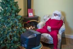 在圣诞节以后的圣诞老人看着电视 免版税图库摄影