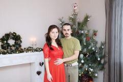 在圣诞节内部的怀孕的妻子和丈夫年轻家庭画象 免版税图库摄影