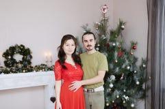 在圣诞节内部的怀孕的妻子和丈夫愉快的年轻家庭画象 图库摄影