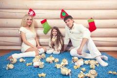 在圣诞节内部,怀孕的美丽的家庭,在一个木房子里 图库摄影
