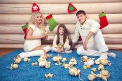 在圣诞节内部,怀孕的美丽的家庭,在一个木房子里 库存照片