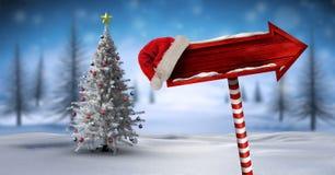 在圣诞节冬天风景和圣诞老人帽子的木路标有圣诞树的 免版税图库摄影
