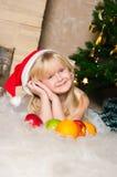 在圣诞节冷杉木之下的女孩 免版税库存照片