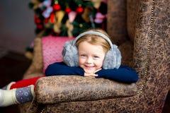 在圣诞节冷杉木附近的女孩在红色口气 库存照片