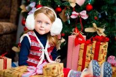 在圣诞节冷杉木附近的女孩在红色口气 免版税库存照片