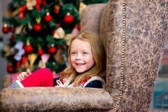 在圣诞节冷杉木附近的女孩在红色口气 免版税库存图片