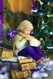 在圣诞节冷杉木附近的女孩 免版税图库摄影