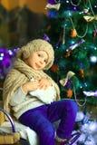 在圣诞节冷杉木附近的女孩 库存图片