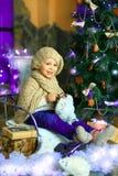 在圣诞节冷杉木附近的女孩 免版税库存照片